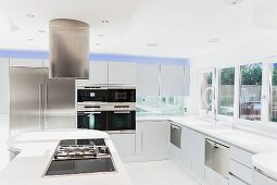 Large, white modern kitchen with island counter below stainless steel extractor hood