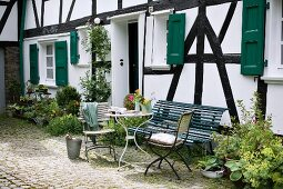 Delicate garden table, garden chairs and bench in front of half-timbered house in summery atmosphere