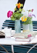 Garden flowers in various vases and books on delicate metal table