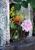 Vase of garden flowers in outdoor fireplace