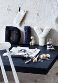 Cardboard letters wrapped in blue and white wool on desk leaing against roughly rendered wall