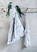 Birds painted on wall rack and simple, white laundry bag decorated with poetry