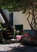 Wooden garden bench and rake in shade next to exterior staircase on facade of house