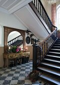Stairwell of manor house with terrazzo floor and staircase with turned wooden balusters