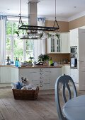 Pale country-house kitchen with island counter, untreated wooden floor and pale blue dining table