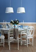Festively set white dining table with silver candlesticks against blue wall and two modern pendant lamps