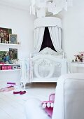 Romantic, white bed with round canopy on white wooden floor; various artworks leaning against wall on floating shelves