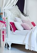 Romantic, white canopied bed with many scatter cushions in various pastel shades