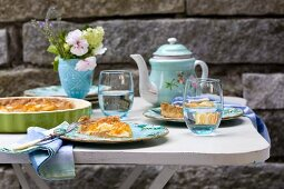 Apricot cake and vintage china crockery on coffee table on terrace