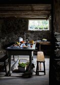 Bread and cheese on wooden table and rustic bench in semi-basement room with stone walls