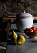 Pears next to bowl of tomatoes and white, vintage enamel pot with lid on wooden table