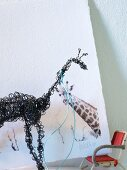 Black, wire giraffe sculpture in front of picture of giraffe on white background