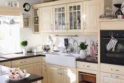 Cream fitted kitchen with panelled doors and large Belfast sink