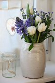 Spring bouquet of white tulips, blue hyacinths and forget-me-nots in simple ceramic jug in front of kitchen curtain with love-heart decorations