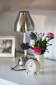 Shabby chic arrangement on bedside table with metal lamp, alarm clock and posy of spring flowers