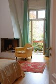 Yellow-covered, antique armchair next to fireplace in bedroom and open balcony door with a view