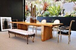 Essplatz mit verschiedenen Sitzmöbeln aus verschiedenen Stilen vor patioartigem Innenhof mit terrassierter Bepflanzung