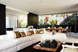 Langes Sofa mit weissen und goldenen Kissen gegenüber rustikalem Bodentisch, im Hintergrund Essplatz vor bepflanztem Patio