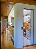 Galley kitchen installation with rounded corners and open sliding door showing kitchen counter: serving hatch and Thonet bar stools at counter on one side