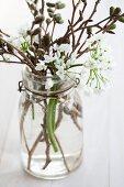 Einmachglas mit Bügelverschluss gefüllt mit Allium und Erlenzweigen
