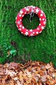 Decorative red wreath with white stars on mossy tree trunk above autumn leaves