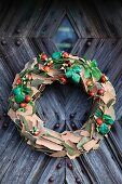 Decorative wreath made from pieces of bark and rosehips hanging on rustic wooden door