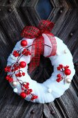 Red berries and Christmas baubles on decorative wreath of white felt on rustic front door