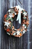 Festive decorative wreath made of pieces of bark on wooden wall