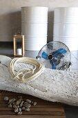 Aufgewickeltes Seil auf weiss gekalktem Baumstamm vor Ventilator am Boden und weiss lackierte Metallfässer im Hintergrund