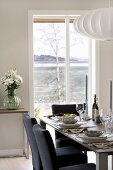 Dark blue upholstered chairs around festively set dining table in front of French doors with view of Norwegian skerry coast