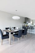 Dining area in muted shades and clean, Scandinavian style in open-plan interior with breakfast in bar