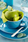 Green apple in blue cup and leaf-shaped sweets on plate