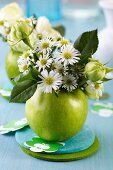 Green apple used as vase for posy