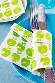 Cutlery wrapped in paper napkin with apple pattern on blue plate