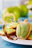 Apple-shaped pastry cutter on plate of biscuits