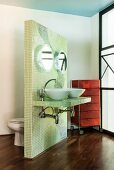 Twin washstand angled towards window with toilet on back of free-standing partition with lime green mosaic tiles