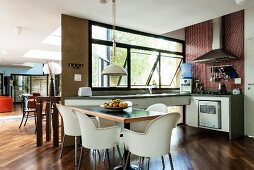 Dining area with sparsely furnished kitchen along two walls in light-flooded, open-plan interior