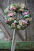 Wreath of flowers with hydrangeas and sprigs of berries hanging on wooden lath