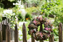 Wreath of hydrangea flowers and branches of berries on paling fence