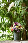 Summery bouquet in ornate zinc pot below white buddleia