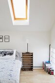 Attic bedroom with upturned fruit crate as bedside table and pillow with Moomins print