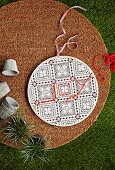 Round door decoration with lace pattern, partly embroidered with red wool thread