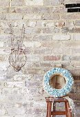 Jute wreath with pastel blue buttons stuck in front of a rustic brick wall, next to it stylized animal trophy decorated with fairy lights