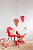 Pinatas hung over a red armchair and wrapped presents next to sweets on sisal carpets