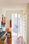 Bunte Taschen und Schals an der Wand in einer hellen Diele mit geöffneter Glastür