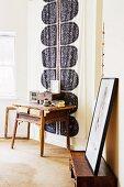 Rustikaler Holztisch vor Wandbehang im Schlafzimmer