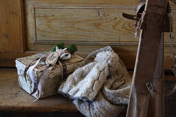 Knitted hat and gift in birch bark box on wooden bench next to vintage skis