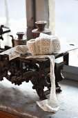 Ball of fabric ribbon and old weights on set of old scales on windowsill