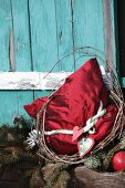 Red silk cushion with vintage Christmas decoration in front of turquoise cabin window shutter