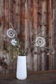 White crocheted stars hanging from twigs in white china vase in front of rustic wooden wall; vintage Christmas atmosphere